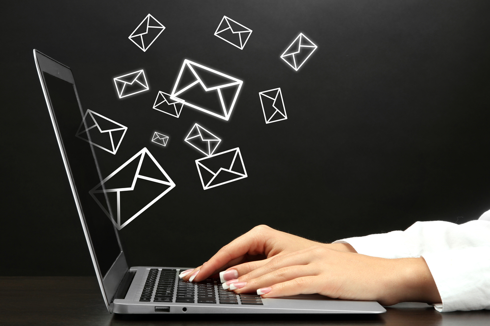 Client success shown through many emails being sent from a laptop