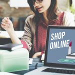 """Two Women meeting with Laptop that reads """"Shop Online"""""""