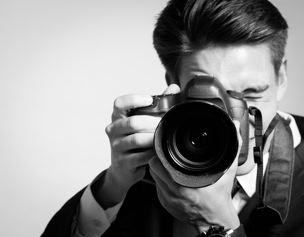 10 Reasons Why Your Business Needs Professional Photography- Young man using a professional camera