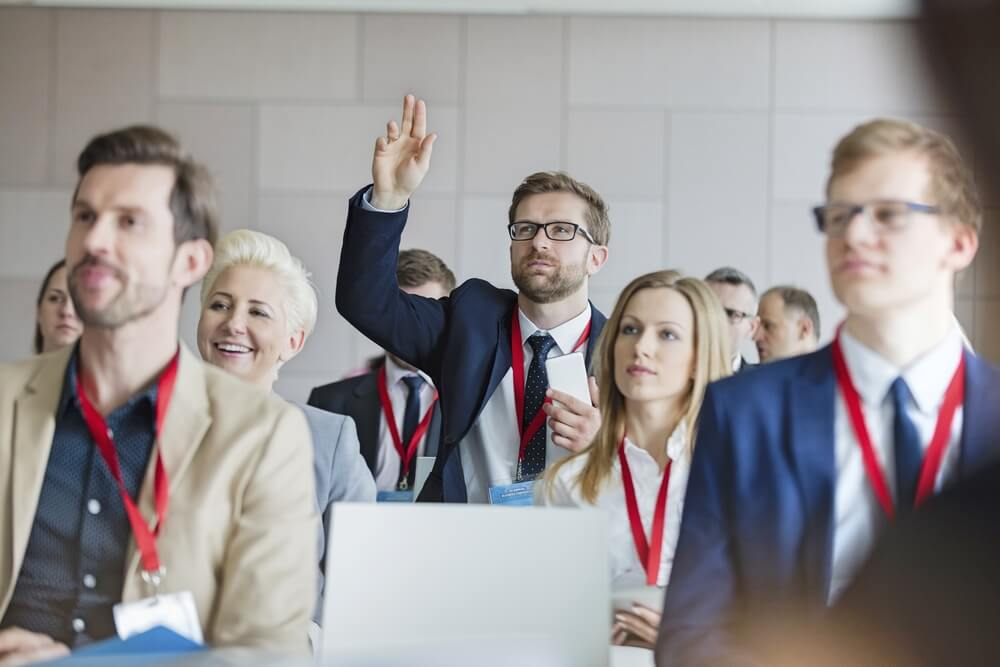 Businessman raising hand during seminar at seminar