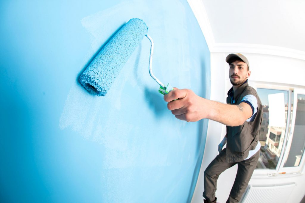 Painter painting a wall blue
