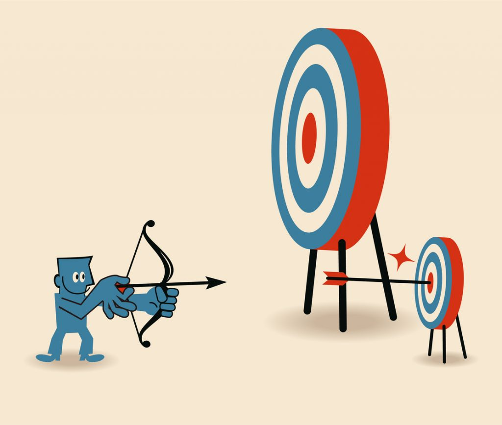 Businessman aiming at smaller target and shooting on Bull's-Eye of dartboard