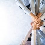 Business people with their hands stacked showing teamwork.